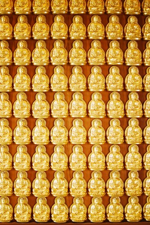Many of Golden Buddha Statue on wooden wall in Chinese Temple photo
