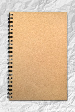 Grunge brown cover notebook on wrinkled paper background photo