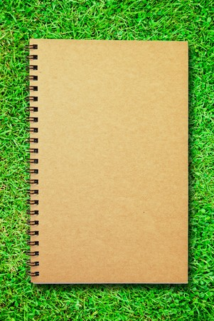 brown cover notebook on green grass field photo