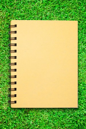 small notebook on green grass field photo