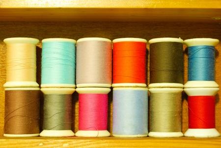 hilo rojo: coloridos bobina de hilo en estanter�a de madera vintage