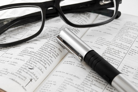 closeup of old dictionary and black glasses with pen photo