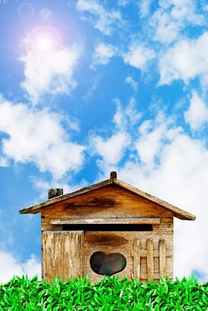 old wood house postbox on beautiful sky and grass field background photo