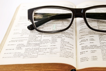 dictionary definition: closeup of old dictionary and black glasses