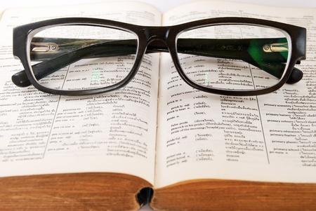 defined: closeup del vecchio dizionario e occhiali neri