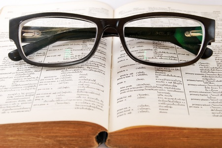 old english letters: closeup of old dictionary and black glasses