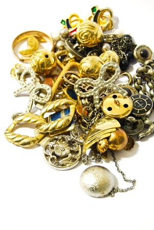 pile of golden silver accessories and jewelry closeup isolated on white background