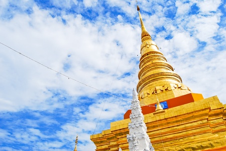 Golden Pagoda in Buddha temple on the beautiful cloudy sky , Asia , Thailand photo