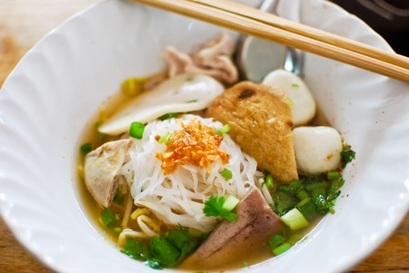 asian style noodle with pork , fish ball and vegetables photo