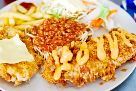 closeup of deep fry steak with spaghetti and french fries set photo