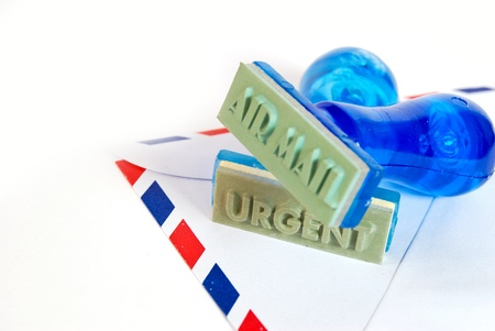 urgent letter on rubber stamp on air mail envelope on white background photo