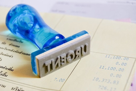 urgent letter on rubber stamp with business cash receipt background photo