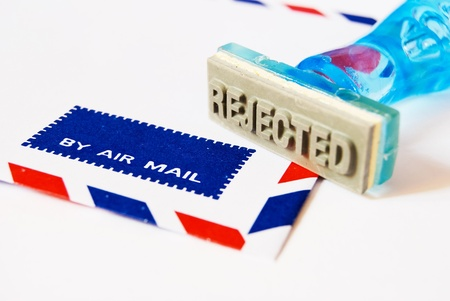 reject letter on rubber stamp with air mail envelope background photo