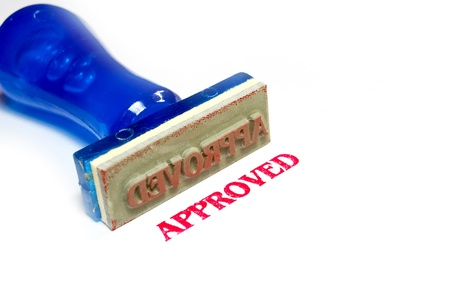 approved letter on blue rubber stamp isolated on white background photo