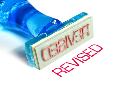 revised letter on blue rubber stamp isolated on white background photo