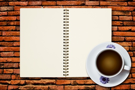 White cup of coffee and blank page notebook on brick wall background photo
