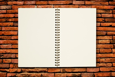block note: blank page notebook open on brick wall background