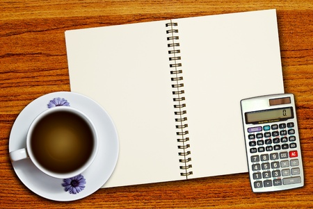 White cup of coffee and calculator on blank page notebook on wood table background photo