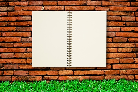 blank page notebook open on brick wall background and fresh green grass Stock Photo - 8801517