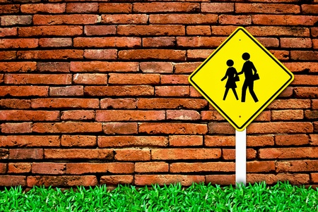 school warning traffic symbol sign on brick wall background and grass field photo
