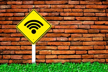 wi-fi internet traffic symbol sign on brick wall background and grass field photo