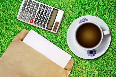 White cup of coffee and brown envelope document with calculator on fresh green grass background photo