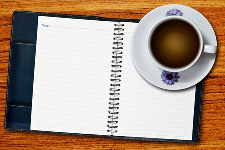 White cup of coffee and blank page notebook on wood table background photo