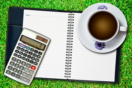White cup of coffee and blank notebook with calculator on fresh green grass background photo