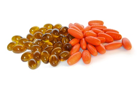 brown fish oil gel capsue and vitamin pills closeup on white background photo
