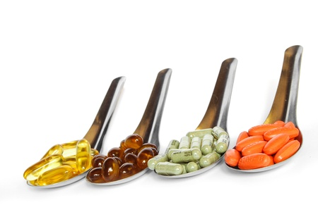 spoon with colorful vitamin medicine pills on white background photo