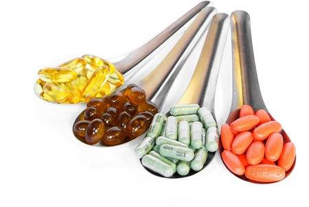 medicamentos: cuchara con p�ldoras de vitamina colorido medicina sobre fondo blanco Foto de archivo