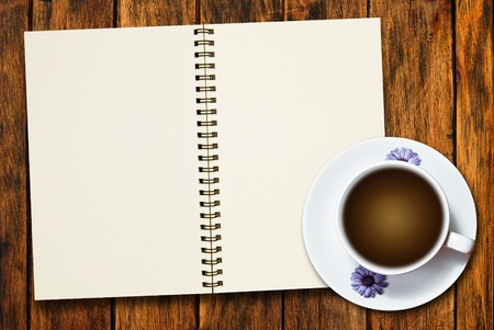 cup of coffee and blank notebook on natural wood texture background photo