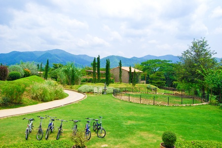 bikes on green grass field farm land with mountain background in resort photo