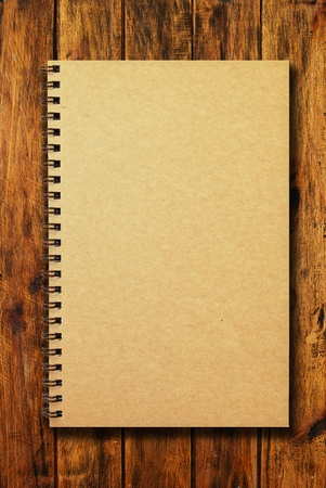 brown cover notebook on natural wood texture background photo