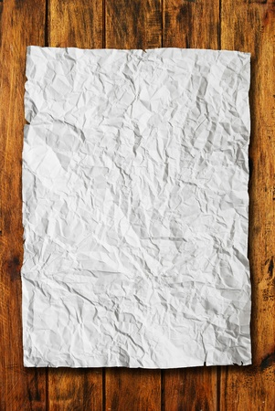 White crumpled paper on natural wood texture background photo