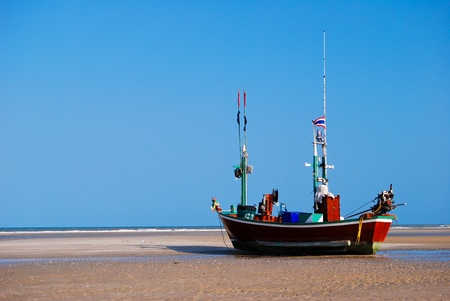 fisherman boat on the sea shore , with bright blue sky background photo
