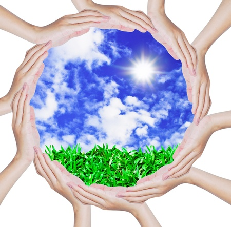 Hands forming a circle shape around blue sky and green grass background Stock Photo