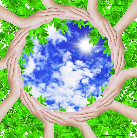 Hands forming a circle shape around blue sky and green leaf background , safe the nature conceptual Stock Photo - 9400490