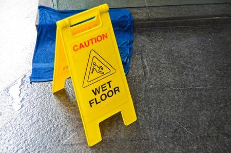 Caution wet floor warning sign on floor background photo