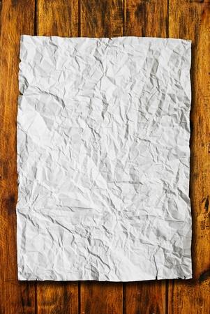 feuille froiss�e: Papier chiffonn� sur fond de texture bois