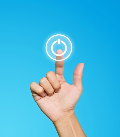 Hand pressing power button on blue background photo