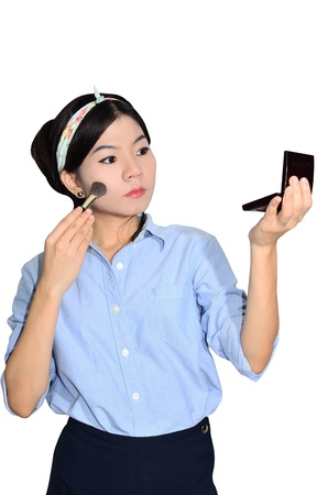 Portrait of asian woman applying make up on white background photo
