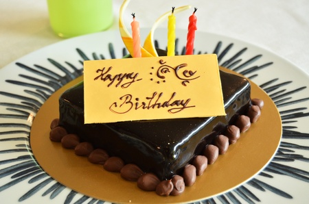 shaped: Chocolate birthday cake with Happy birthday letter tag Stock Photo