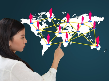 Business woman presenting social network on world map photo