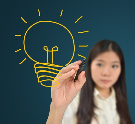 Business woman drawing light bulb of idea