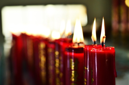 Big red burning candles in Buddhist temple photo