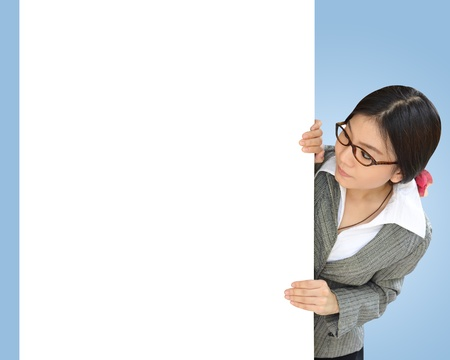 Business woman peeping over white billboard background photo
