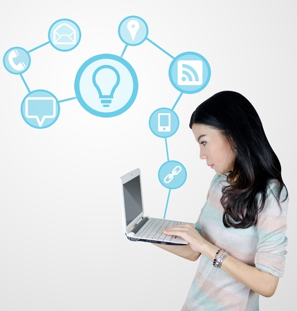 Young Asian woman using laptop computer with technology icons and symbols photo