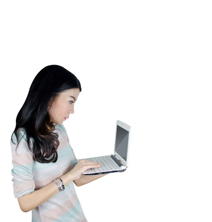 Young Asian woman using laptop computer on white background photo