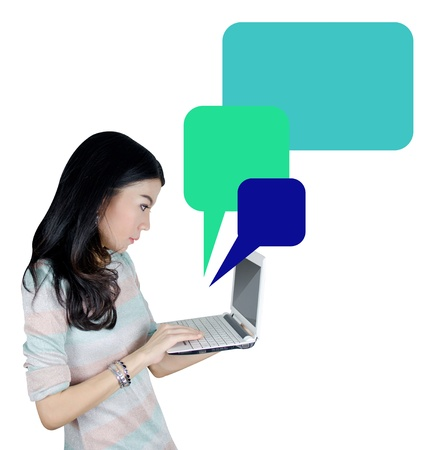 Young Asian woman using laptop computer with speech bubble icon photo